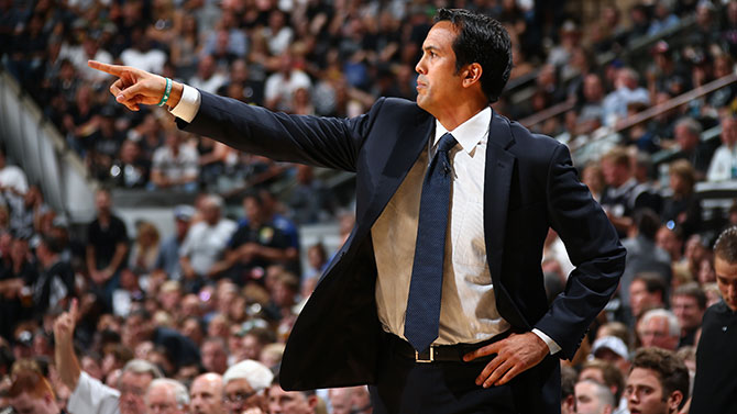 Coach Spoelstra communicating with players from the sideline during a game.